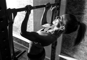 mujer entrenando con barra dominadas
